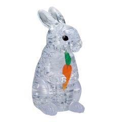 Kolmiulotteinen istuva pupu palapeli. Pupu pitää porkkanasta kiinni. Pupu on väriltään vaalea/läpinäkyvä. Porkkana on väriltään oranssi ja versot vihreät.