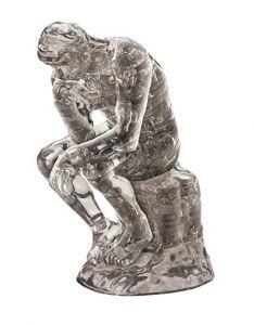 Kolmiulotteinen palapeli. Miettivä henkilö, joka istuu kiveä mallintavalla jalustalla. Palapeli on väriltään harmaa.